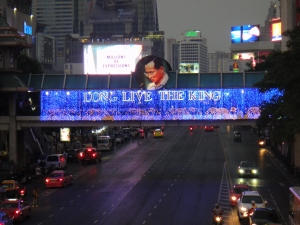 "Lighted ""Long Live the King"" banner on a skywalk across a city street"