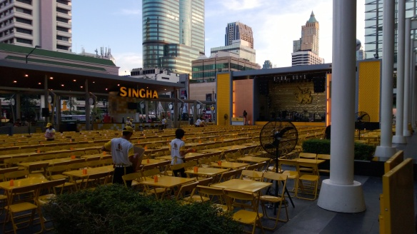 The Singha Beer Park outside CentralWorld mall.  Yellow tables, thousands of yellow chairs, and large stage in center-right of pic.
