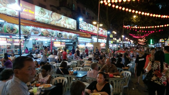 Typical street hawker food stand, with tables/chairs set up in the street.