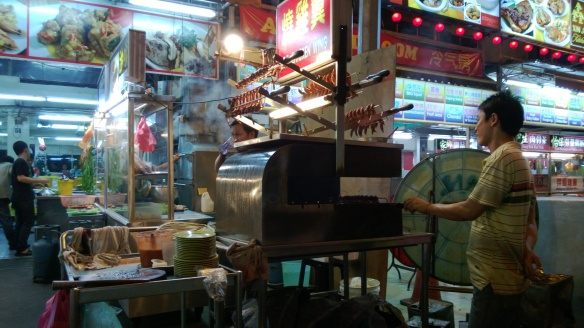 A cook at the hawker street stall, barbecuing something.  Probably chicken feet, as those seemed to be pretty popular there.
