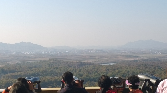 "Looking into North Korea.  Where the trees stop is where the border is. White buildings in middle of pic is the ""propaganda village""."