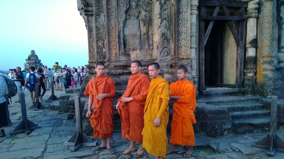 """Monks at Phnom Bakheng Temple... aka, the """"sunset temple"""" where crowds of visitors climb a long pathway up a hill to the temple, then climb several sets of near-vertical stairs to get to the top of the temple to watch the amazing sunsets."""