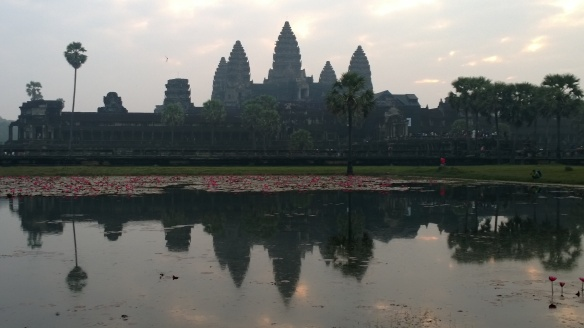 The stunning Angkor Wat temple at sunrise, reflected in a pond in front of the temple.