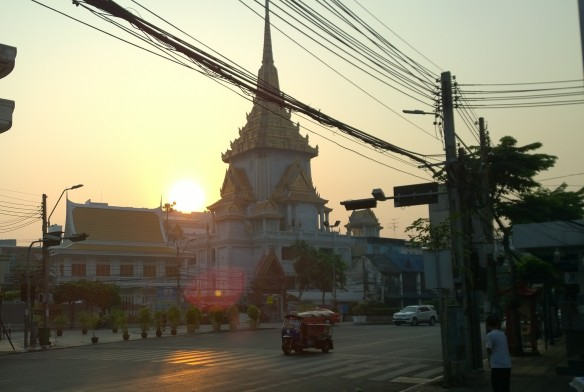 Wat Traimit (Temple of the Golden Buddha) at sunrise, with a tuk yuk cruising by