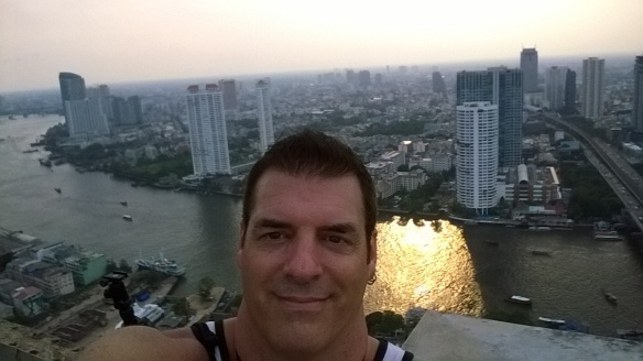 Selfie at the top of the building, with the sunset reflecting on the river below